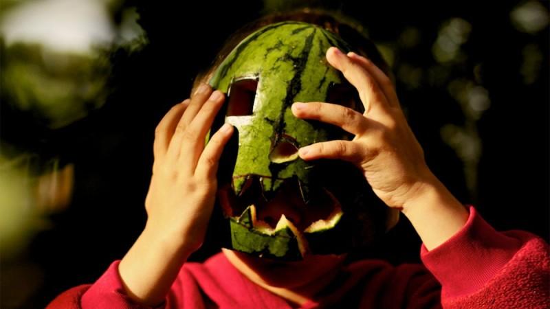 Foto eines Kindes mit Wassermelone als Jack-O-Laterne-Maske vor dem Gesicht