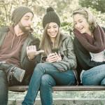 Geschenke-App givie steht ab sofort auf Google Play zum Download bereit - Ein Mann und zwei Frauen auf der Parkbank, lachend auf ein Smartphone schauend